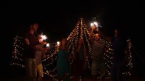 Νέοι που έχουν το κόμμα παραλιών νύχτας και που χορεύουν με τα sparklers απόθεμα βίντεο