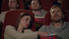 Νέοι που απολαμβάνουν την ταινία στον κινηματογράφο Ζεύγος που τρώει popcorn και που προσέχει τον κινηματογράφο απόθεμα βίντεο