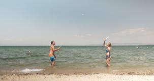Νέοι που απολαμβάνουν την αντισφαίριση στη θάλασσα απόθεμα βίντεο