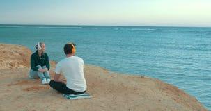 Νέοι που απολαμβάνουν τη θέα και τη μουσική θάλασσας απόθεμα βίντεο
