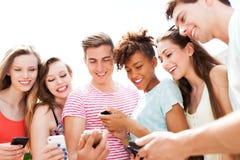 Νέοι που εξετάζουν τα smartphones Στοκ Εικόνες