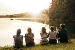 Νέοι που κάθονται σε μια σειρά από μια λίμνη Στοκ Φωτογραφία