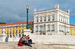 Νέοι που κάθονται στη σκάλα που οδηγεί στον ποταμό Tagus στο τετράγωνο εμπορίου στοκ φωτογραφία