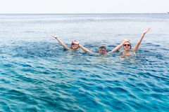 Νέοι που κολυμπούν στη θάλασσα που αυξάνει τα χέρια τους επάνω Στοκ εικόνες με δικαίωμα ελεύθερης χρήσης