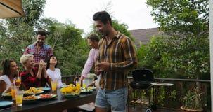 Νέοι που μιλούν τη συνεδρίαση στη συλλογή ομάδας φίλων σχαρών επιτραπέζιου μαγειρέματος στην επικοινωνία θερινών πεζουλιών φιλμ μικρού μήκους