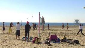 Νέοι που παίζουν ένα παιχνίδι της πετοσφαίρισης στην παραλία απόθεμα βίντεο