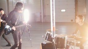 Νέοι που παίζουν τα όργανα στο φωτεινό δωμάτιο Ένα soloist με την κιθάρα που έρχεται πιό κοντά σε έναν τυμπανιστή, που ρωτά κάτι απόθεμα βίντεο