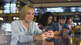 Νέοι που χρησιμοποιούν τα κινητά τηλέφωνα στο φραγμό, που διαβάζει τα μηνύματα στη χρονολόγηση app, η ελεύθερη WI-Fi απόθεμα βίντεο