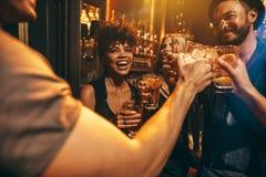 Νέοι που ψήνουν τα ποτά στο νυχτερινό κέντρο διασκέδασης στοκ εικόνα με δικαίωμα ελεύθερης χρήσης