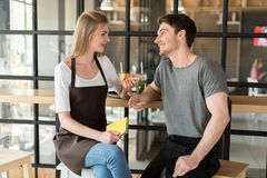 νέοι σερβιτόρος και σερβιτόρα που έχουν τη συνομιλία κατά τη διάρκεια του σπασίματος στην εργασία Στοκ Φωτογραφίες