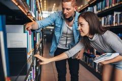 Νέοι σπουδαστές που βρίσκουν τα βοηθητικά βιβλία στην πανεπιστημιακή βιβλιοθήκη Στοκ Φωτογραφίες