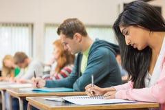 Νέοι σπουδαστές που γράφουν τις σημειώσεις στην τάξη Στοκ εικόνες με δικαίωμα ελεύθερης χρήσης