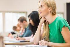 Νέοι σπουδαστές που γράφουν τις σημειώσεις στην τάξη Στοκ Φωτογραφία