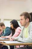 Νέοι σπουδαστές που γράφουν τις σημειώσεις στην τάξη Στοκ Φωτογραφίες