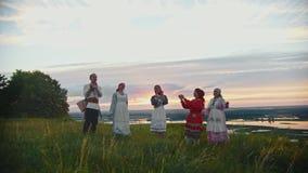 Νέοι στα ρωσικά παραδοσιακά ενδύματα που έχουν τη διασκέδαση στον τομέα - χορός και που χτυπούν τα χέρια τους απόθεμα βίντεο