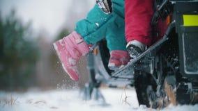 Νέοι στα φωτεινά ενδύματα που παίρνουν αργά στο όχημα για το χιόνι φιλμ μικρού μήκους