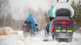 Νέοι στα φωτεινά ενδύματα που παίρνουν στα οχήματα για το χιόνι Έναρξη μιας φυλής ταχύτητας κίνηση αργή φιλμ μικρού μήκους