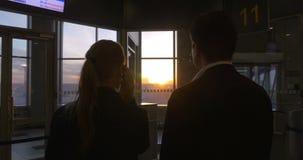 Νέοι στον αερολιμένα στο ηλιοβασίλεμα φιλμ μικρού μήκους