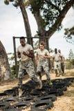 Νέοι στρατιωτικοί στρατιώτες που ασκούν τη σειρά μαθημάτων εμποδίων ελαστικών αυτοκινήτου Στοκ Εικόνα
