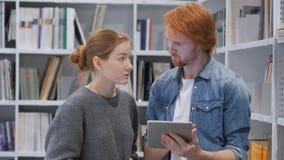 Νέοι συμπαίκτες, σπουδαστές που κοιτάζουν βιαστικά στο PC ταμπλετών στη βιβλιοθήκη, εργασία στοκ εικόνα με δικαίωμα ελεύθερης χρήσης