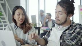 Νέοι συνάδελφοι ομάδας που συζητούν μαζί το δημιουργικό πρόγραμμα κατά τη διάρκεια των σύγχρονων συναδέλφων διαδικασίας εργασίας  απόθεμα βίντεο