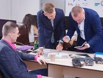 Νέοι συνάδελφοι που εργάζονται στο γραφείο που κάμπτει πέρα από έναν πίνακα Στοκ εικόνες με δικαίωμα ελεύθερης χρήσης