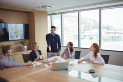 Νέοι συνέταιροι που συζητούν στη συνεδρίαση στοκ φωτογραφία με δικαίωμα ελεύθερης χρήσης