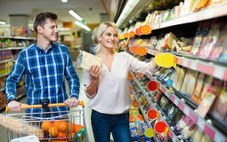 Νέοι σύζυγοι που αγοράζουν το τυρί Cheddar στο τμήμα τυριών Στοκ Εικόνες