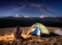 Νέοι τουρίστες ζευγών που έχουν ένα υπόλοιπο στη στρατοπέδευση τη νύχτα κάτω από το όμορφο σύνολο νυχτερινού ουρανού των αστεριών Στοκ Φωτογραφίες