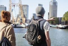 Νέοι τουρίστες ζευγών που κοιτάζουν και που δείχνουν το λιμάνι πόλεων του Ρότερνταμ, μελλοντική έννοια αρχιτεκτονικής, βιομηχανικ Στοκ Εικόνα