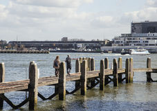 Νέοι τουρίστες ζευγών που κοιτάζουν και που δείχνουν το λιμάνι πόλεων του Ρότερνταμ, μελλοντική έννοια αρχιτεκτονικής, βιομηχανικ Στοκ Εικόνες