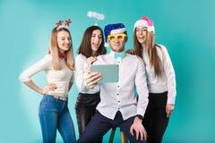 Νέοι υπάλληλοι επιχείρησης χειμερινών γραφείων Χριστουγέννων θέματος έτους Ομάδα 4 νέα καυκάσια αστεία καπέλα διακοπών επιχειρησι στοκ εικόνες