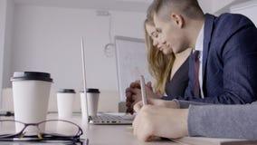 Νέοι υπάλληλοι που εργάζονται στον πίνακα με το lap-top στο σύγχρονο γραφείο φιλμ μικρού μήκους