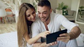 Νέοι υπολογιστής και φιλί ταμπλετών χρήσης χαριτωμένων και ζευγών αγάπης καθμένος στο κρεβάτι στην κρεβατοκάμαρα στο πρωί απόθεμα βίντεο