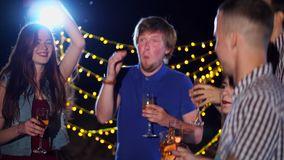 Νέοι φίλοι με τη σαμπάνια στο χορό χεριών τους ενεργά στα discos τη νύχτα απόθεμα βίντεο
