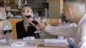 Νέοι φίλοι που έχουν τη διασκέδαση στο εστιατόριο που πίνει το κόκκινο κρασί Έννοια φιλίας νεολαίας απόθεμα βίντεο