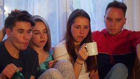Νέοι φίλοι που κάθονται στο σπίτι, καφές κατανάλωσης και κατανάλωση των πρόχειρων φαγητών απόθεμα βίντεο