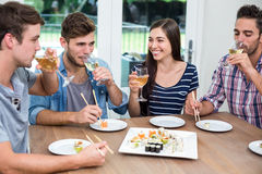 Νέοι φίλοι που πίνουν το κρασί ενώ έχοντας τα σούσια Στοκ φωτογραφία με δικαίωμα ελεύθερης χρήσης