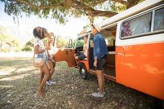 Νέοι φίλοι που υπερασπίζονται το φορτηγό τροχόσπιτων στη θέση για κατασκήνωση στοκ φωτογραφία με δικαίωμα ελεύθερης χρήσης