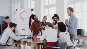 Νέοι χαρούμενοι πολυεθνικοί επιχειρηματίες που συναντιούνται σε σύγχρονο υγιές γραφείο, γελώντας με το θηλυκό αφεντικό αργή κίνησ απόθεμα βίντεο