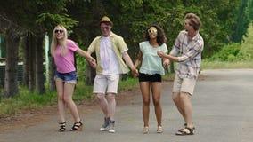 Νέοι χαρούμενοι φίλοι που χορεύουν και που έχουν τη διασκέδαση στο πάρκο, καλοκαιρινές διακοπές, νεολαία απόθεμα βίντεο
