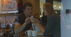 Νέοι χρησιμοποιώντας το έξυπνο τηλέφωνο και μιλώντας στον καφέ φιλμ μικρού μήκους
