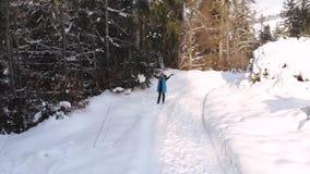 Νέοι όμορφοι περίπατοι κοριτσιών στο χιονώδες χειμερινό δάσος είναι ευτυχής και εύθυμη Το κορίτσι ρίχνει το χιόνι πέρα από το κεφ φιλμ μικρού μήκους