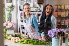 Νέοι multiethnic ανθοκόμοι που τακτοποιούν τα όμορφα φρέσκα λουλούδια στο ανθοπωλείο Στοκ Εικόνα