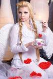 Νέος άγγελος κοριτσιών ομορφιάς που κρατά ένα φλυτζάνι Στοκ φωτογραφία με δικαίωμα ελεύθερης χρήσης