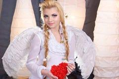 Νέος άγγελος κοριτσιών ομορφιάς που κρατά την καρδιά Στοκ φωτογραφίες με δικαίωμα ελεύθερης χρήσης