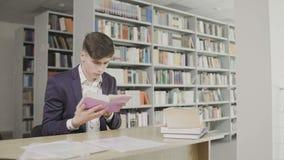 Νέος άνδρας σπουδαστής που διαβάζει ένα βιβλίο σε μια βιβλιοθήκη Άτομο σε ένα βιβλίο ανάγνωσης κοστουμιών στο υπόβαθρο ραφιών φιλμ μικρού μήκους