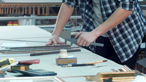 Νέος άνδρας εργαζόμενος στο εργαστήριο πλαισίων που λειτουργεί στο γραφείο Στοκ Φωτογραφίες