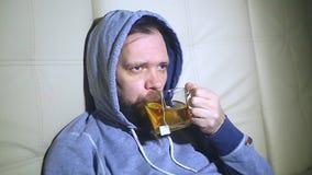 Νέος άρρωστος άνδρας που πίνει το καυτό τσάι στο σπίτι, κινηματογράφηση σε πρώτο πλάνο απόθεμα βίντεο