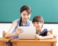 Νέος δάσκαλος που βοηθά το παιδί με το μάθημα υπολογιστών Στοκ Φωτογραφία